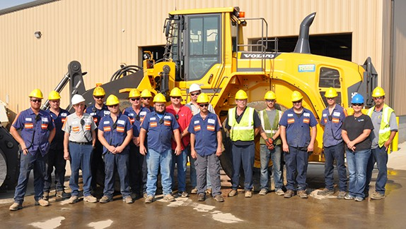 group of site workers in front of machine